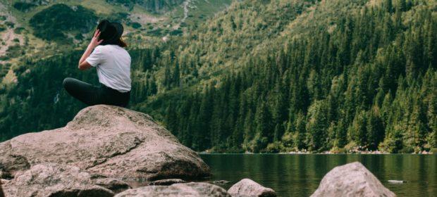 Nachhaltig Reisen See Mensch auf Felsbrocken