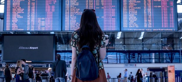 Reisen als Karrierebooster, Flau steht am Flughafen vor der Schalttafel