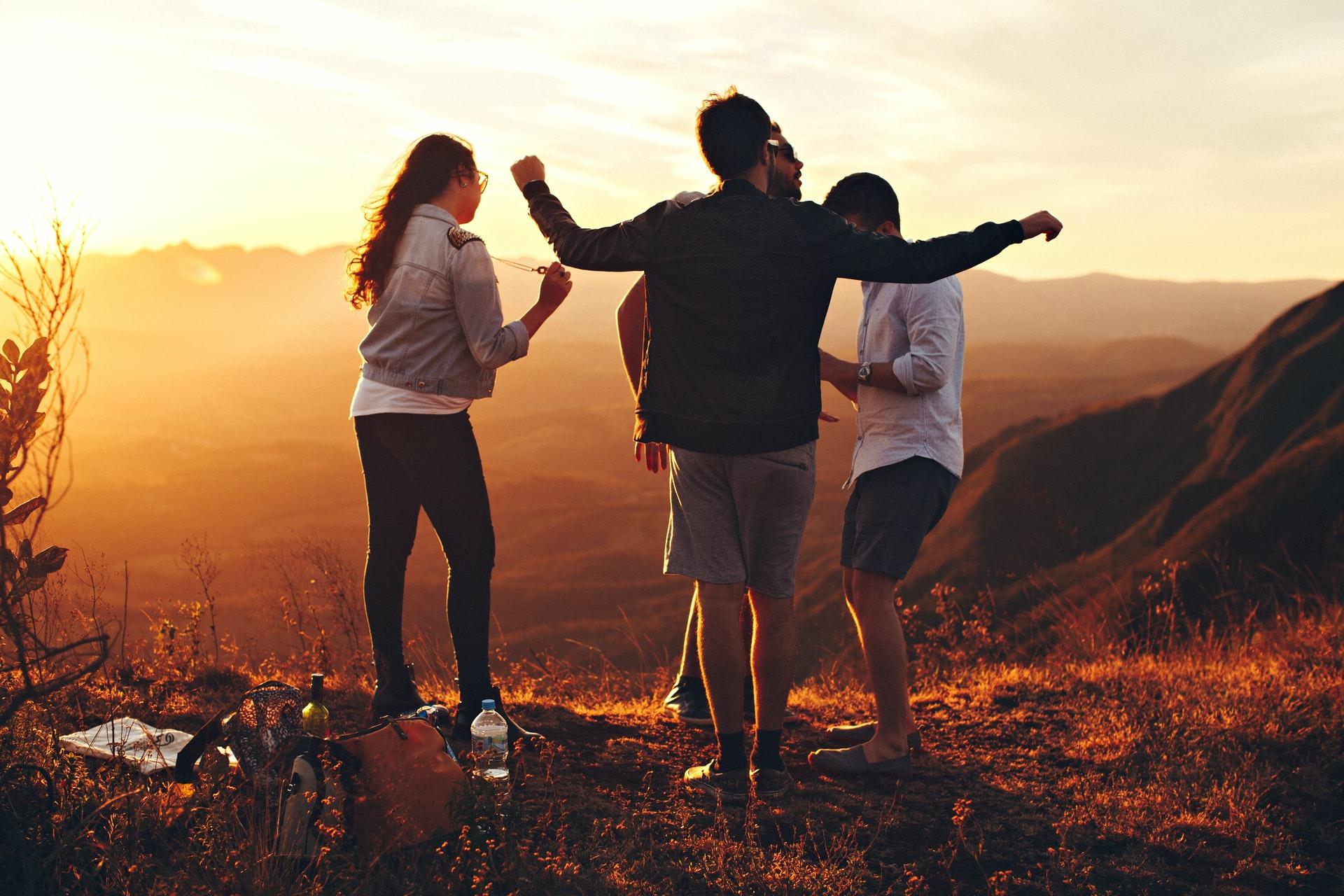 Eine Gruppe von Personen tanzt bei Sonnenuntergang