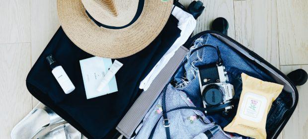 Reisevorbereitung. Gepackter Koffer mit allen wichtigen Reiseutensilien.