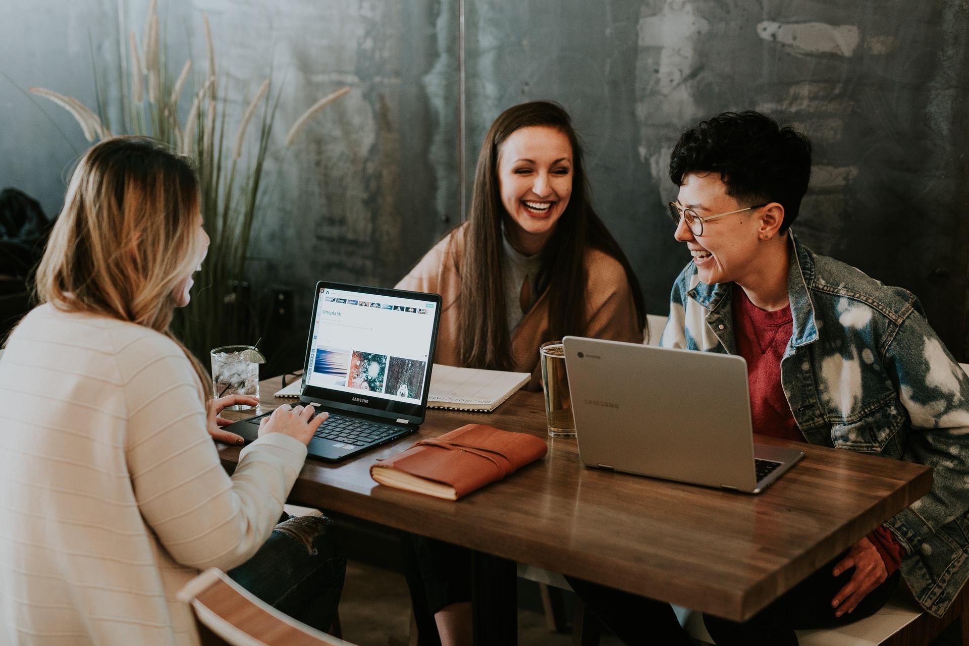Drei Personen am Laptop unterhalten sich untereinander