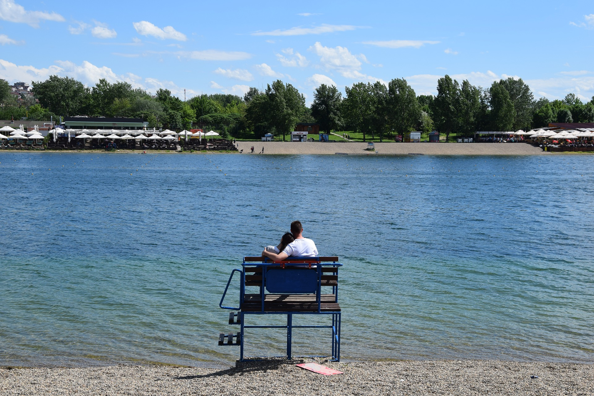 Ein Paar sitzt auf einer Bank am Save-See